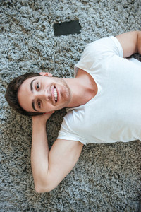 Vertical image of happy man lying on the floor and looking at camera. Top view