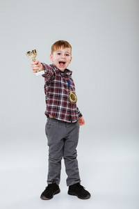 Vertical image of Happy young boy in shirt holding chalice and looking at camera with open mouth. Isolated gray background