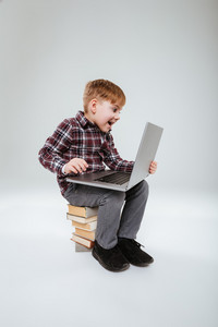 Vertical image of laughing young boy in shirt using laptop and sitting on books. Isolated gray background