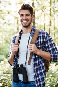 Vertical image of man in forest. guy in shirt with binoculars and backpack