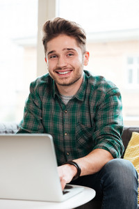 Vertical image of man sitting on sofa with laptop and looking at camera in office. Cowerking