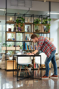 Vertical image of man standing near the table and and looking at laptop in office. Full length. Coworking