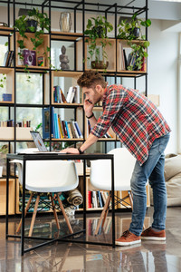 Vertical image of man standing near the table, looking at laptop and taking on phone in office. Full length. Coworking