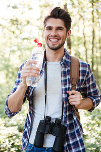 Vertical image of man with water in forest. guy in shert with binoculars and backpack