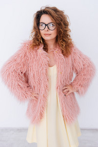 Vertical image of pretty woman in glasses and pink fur coat standing in studio with arms at hip. Isolated gray background
