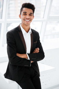 Vertical image of smiling african business man in black suit standing near the window with arms crossed in office and looking at camera
