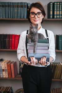 Vertical image of Smiling Authoress in glasses and white shirt holding books with cat on them and looking at camera