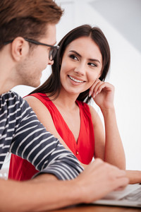 Vertical image of smiling couple sitting by the table with laptop in office. Couple looking each other