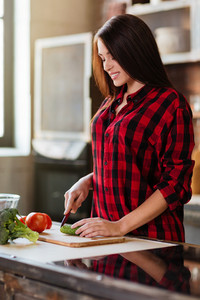 Vertical image of smiling cute woman in red shirt cooking in kitchen. Side view