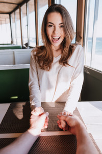 Vertical image of smiling woman sitting on date in cafe near sea, holding hands her man and looking at camera. First-person view