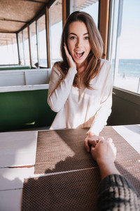 Vertical image of surprised woman sitting by the table on date in cafe near sea with hand on cheek and holding hand her man. First-person view