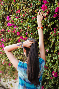 Vertical image of woman in beahwear posing near the flower bush. Back view
