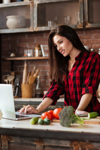 Vertical image of woman in red shirt standing at the table in kitchen with laptop and looking recipes. Side view