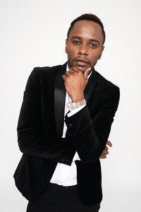 Vertical image of young african man in suit holding hand near the face and looking at camera. Isolated white background