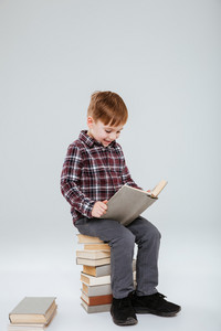 Vertical image of young boy reading book and sitting on books