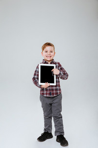 Vertical image of young boy showing blank tablet computer screen. Full length. Isolated gray background