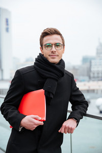 Vertical image of young business man in glasses and warm clothes holding folder and looking at camera outdoors