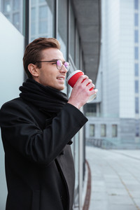 Vertical image of young business man in glasses and warm clothes standing sideways and drinking coffee outdoors