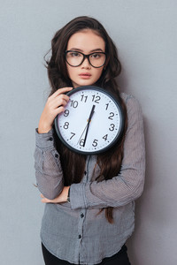 Vertical image of young cute asian woman in glasses holding clock and looking at camera. Isolated gray background