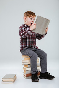 Vertical image of young surprised boy in shirt reading book and sitting on books. Isolated gray background