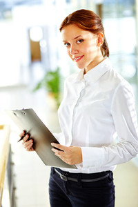 Vertical portrait of a charming business lady smiling at the viewer