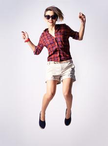 Vertical portrait of a cheerful model enjoying jumping