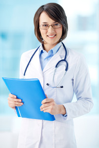 Vertical portrait of a lovely general practitioner holding a folder