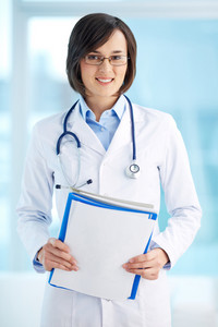 Vertical portrait of a lovely general practitioner holding documents