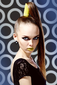Vertical shot of a girl wearing a high ponytail and yellow lipstick