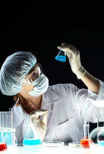 Vertical shot of a woman holding a beaker with blue substance and looking at it