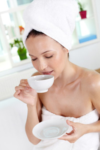 Vertical shot of young woman enjoying tea in spa salon