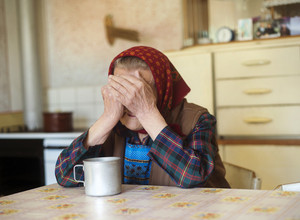 Very old sad woman in headscarf sitting in her countrystyle kitchen