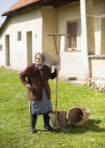 Very old woman in head scarf with garden tools in her back yard