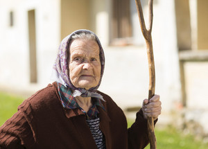 Very old woman in head scarf with rake in her backyard