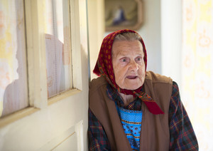 Very old woman is standing by the door and looking to the camera at her country style house