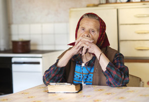 Very old woman wearing head scarf is praying in her country style kitchen
