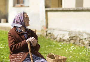 Very old woman with head scarf sitting and relaxing in the garden