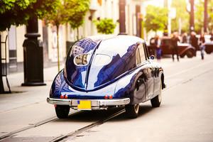 Veteran car street cruise on public roads. rear view, sunny summer day