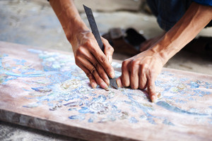 Vietnamese craftsman carving out and painting a floral pattern on a wooden board