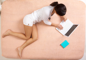 View from above of girl lying on bed and typing on laptop