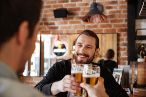 View from back of man clinking glasses with friend on bar