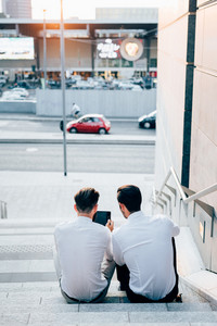 View from behind of two young bearded blonde and black hair modern businessman, sitting on a staircase,  using tablet - technology, business, work concept