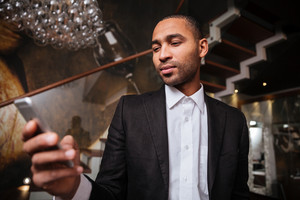 View from below of african man in suit using phone in hotel