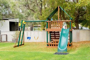 View of kids playground in green backyard garden