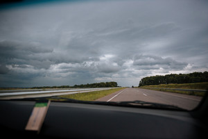 View of the road from windshield of car in cloudly weather