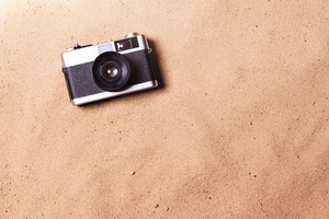 Vintage camera laid on beach. Summer vacation composition. Sand background, studio shot, flat lay. Copy space.