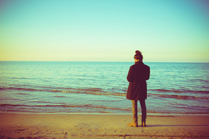 Vintage filtered back view of man standing at the seaside watching the winter sea - pensive, thoughtful, thinking future