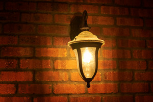 Vintage lamp near old cracked bricks wall