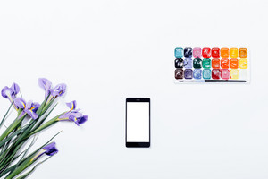 Violet flowers, mobile phone and watercolor paints on a white table top view