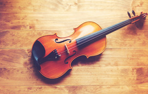 Violin lying on a wooden textured table